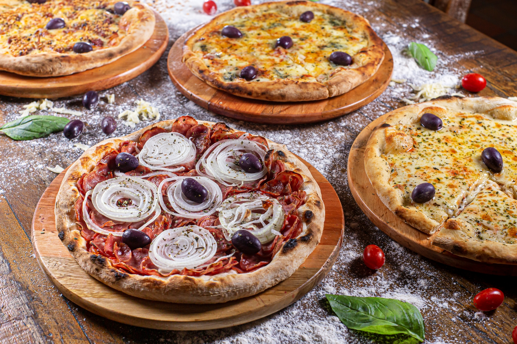 4 pizzas sendo preparadas